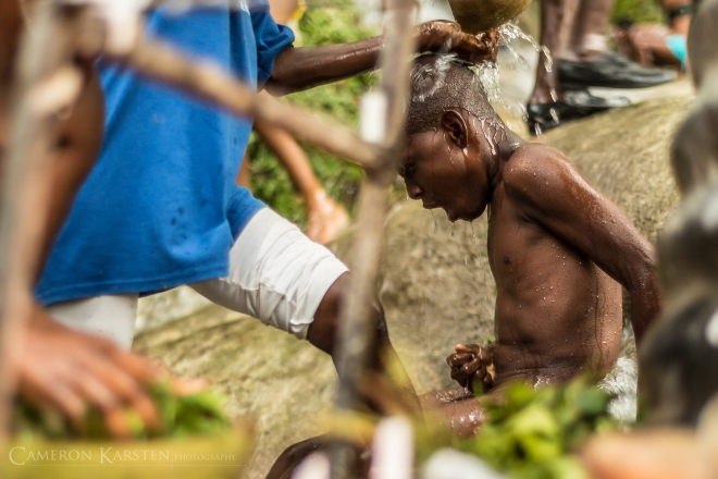 A young boy is bathed by his parents in the sacred waters of Saut d'Eau. He will also be scrubbed with a mixture of herbs including parsley and tree leaves believed to cleanse the body of sins that also bring good luck.