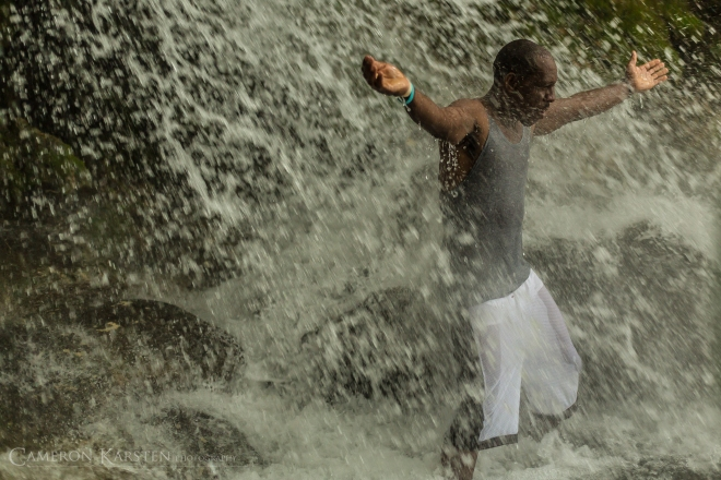 A man spreads his arms under the falls of Saut d'Eau.