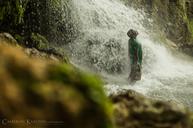 In a moment of solitude, a pilgrim enjoys the cool healing waters of Saut d'Eau.