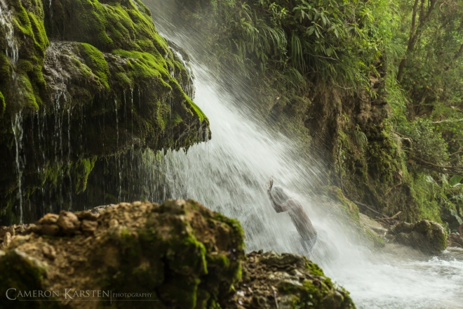 A Haitian bathes and prays in the waterfall of Saut d'Eau during the annual pilgrimage.