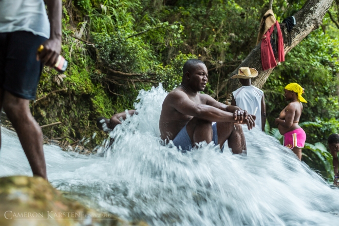 A pilgrim at Saut d'Eau sits still in the rushing waters.