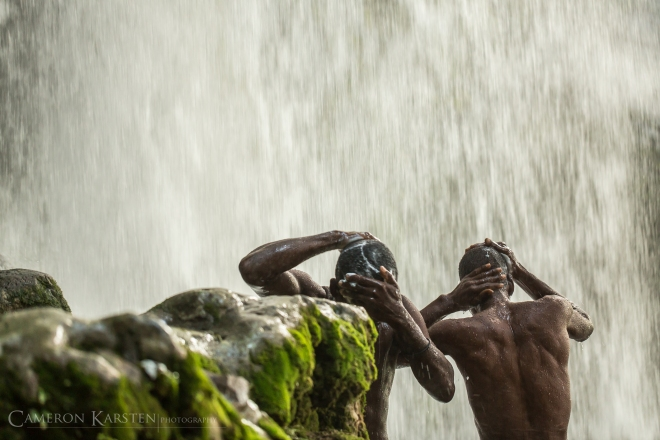 Two pilgrims bathe with soap near the falls of Saut d'Eau.
