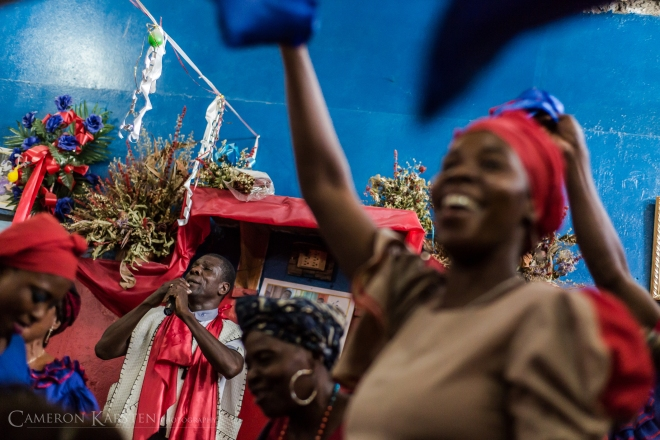 The houngan Sanba Zelle excites his congregation at his hounfour in Montagne Noire outside of Port-au-Prince. Haitian vodou is as much a party for the community as it is a religious celebration. Vodouisants gather to sing and dance, shedding the hardships they face in a post-earthquake Haiti. As of 2011, 61.7% of the population lives below the poverty line.