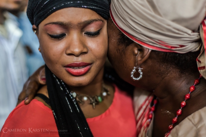 A woman in trance by Ogue Feray embraces another vodouisant. When in trance, vodou spirits are looking to experience the physicality of humanity.